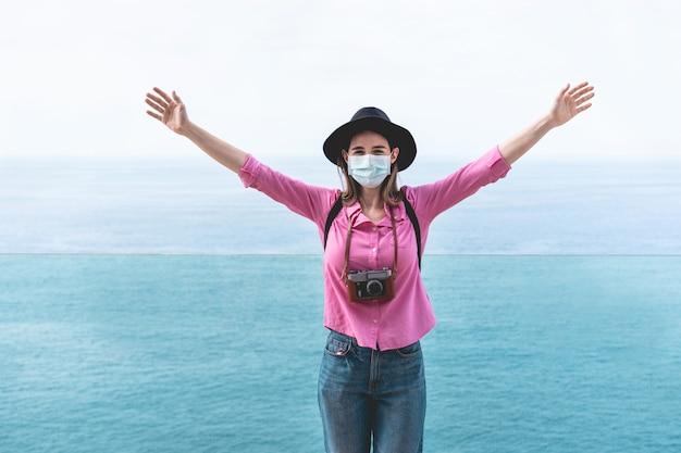 バックグラウンドでオーシャンビューのフェイスマスクを着用しながらヴィンテージの古いカメラを使用して若い観光客女性