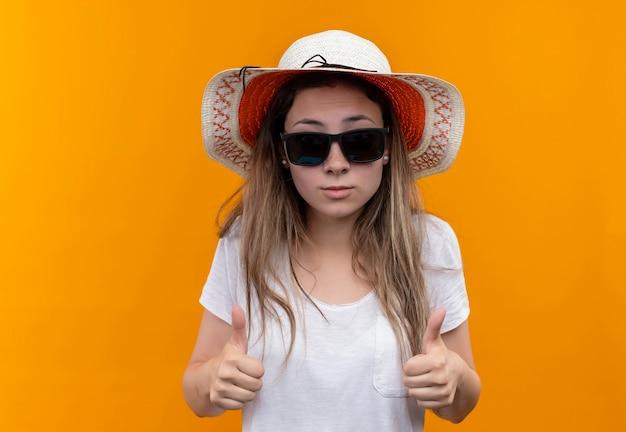 Giovane donna turistica in maglietta bianca che indossa cappello estivo e occhiali da sole neri che mostra i pollici in su in piedi sopra la parete arancione