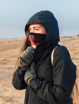 추위로부터 자신을 보호하기 위해 젊은 여행자의 지퍼 재킷.