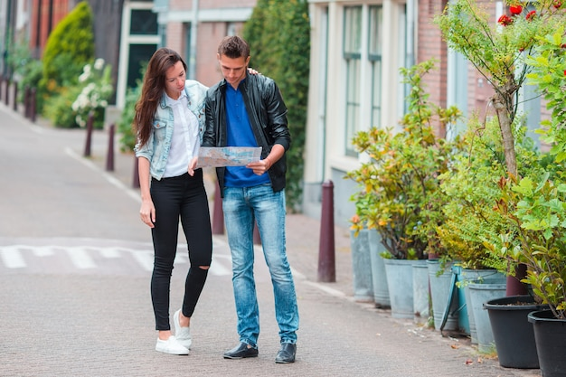 Young tourists couple looking at map in european city