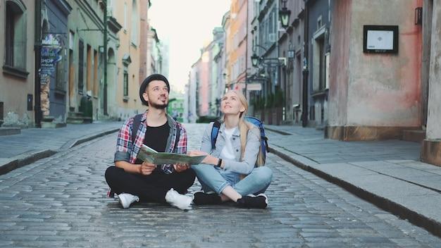 Молодые туристы пара используют карту, сидя на тротуаре и любуясь историческими окрестностями. они взволнованы и улыбнулись.