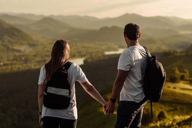 Молодые туристы мужчина и женщина с рюкзаками на вершине горы смотрят на долину и реку