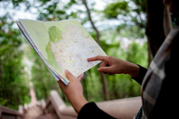 Young tourists and a map with a smile are happy to travel to various locations.