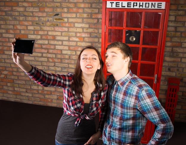 携帯電話で自分撮りをしている象徴的な赤い英国の電話ブースの前でポーズをとる若い観光客