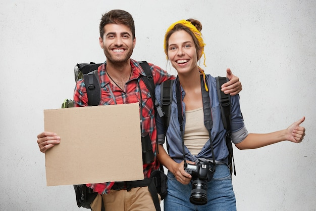 Young tourists posing: smiling man holding blank cardboard and big rucksack embracing his wife who is holding camera and backpack showing ok sign. tourism, travelling concept