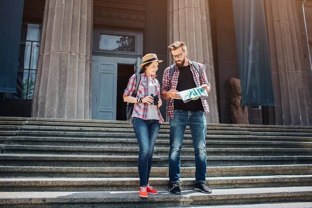 젊은 관광객은 계단에 서 있고지도에 lok. 그들은 가이가 집중되어 있다고 연구합니다. 젊은 여자의 미소입니다. 그녀는 쌍안경을 가지고 있습니다.