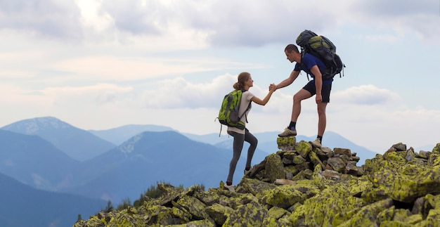 Young tourists with backpacks, athletic boy helps slim girl to clime rocky mountain top against bright summer sky and mountain range scene. tourism, traveling and healthy lifestyle concept.