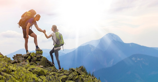 Young tourists with backpacks, athletic boy helps slim girl to clime rocky mountain top against bright summer sky and mountain range. tourism, traveling and healthy lifestyle concept.