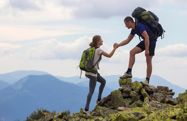 Young tourists with backpacks, athletic boy helps slim girl to clime rocky mountain top against bright summer sky and mountain range .