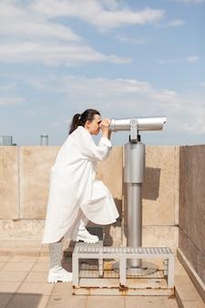 Молодая туристическая женщина, стоящая на башне здания, смотрит в бинокль в телескоп
