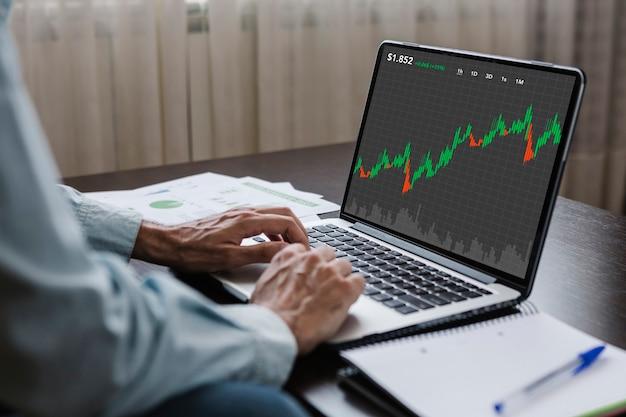 Молодой торговый деловой человек, работающий дома, используя веб-сайт биржи фондовой биржи на ноутбуке
