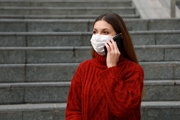 Young trainee woman wearing protective mask near steps using smartphone on break time.