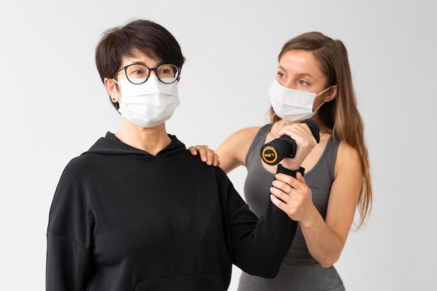 コロナウイルス後の女性の回復を助ける若いトレーナー
