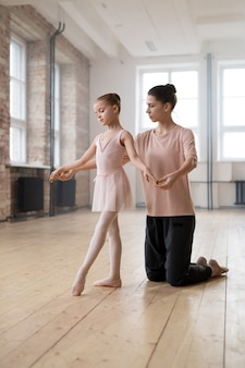 Young trainer showing to her student the right position in ballet during their classes in dance studio