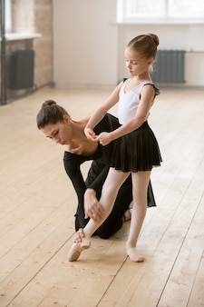 Young trainer showing the right pose to little girl who learning to dance ballet in dance school