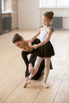 ダンススクールでバレエを踊ることを学ぶ少女に正しいポーズを示す若いトレーナー
