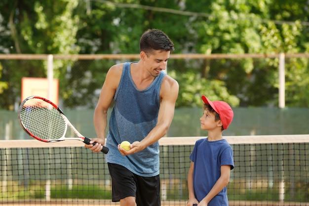 テニスコートで小さな男の子と若いトレーナー