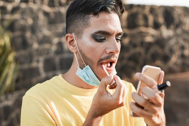 화장을 한 젊은 트랜스젠더 남자는 턱 아래에 안전 얼굴 마스크를 착용하면서 거울이 있는 립글로스를 바르십시오