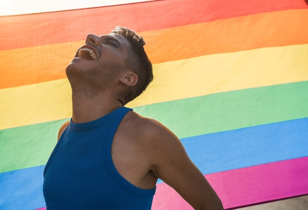 Young transgender man with makeup smiling with lgbt rainbow flag on background
