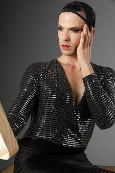 Persona giovane transgender che esamina la vista frontale dello specchio