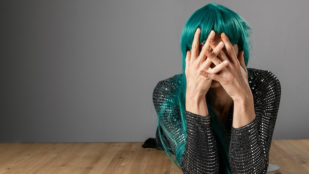 Young transgender person wearing green wig copy space