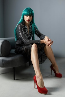 Young transgender person wearing green wig and red shoes