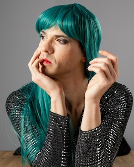 Young transgender person wearing green wig