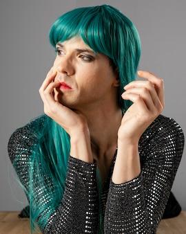 緑のかつらを身に着けている若いトランスジェンダーの人