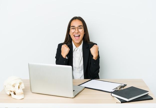 Женщина молодого травматолога азиатская изолированная на белой предпосылке аплодисменты беззаботная и взволнованная. концепция победы.
