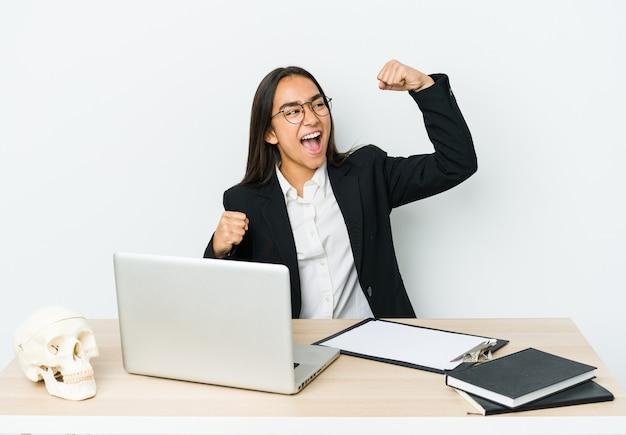 Женщина молодого травматолога азиатская изолированная на белой предпосылке поднимая кулак после победы, концепции победителя.