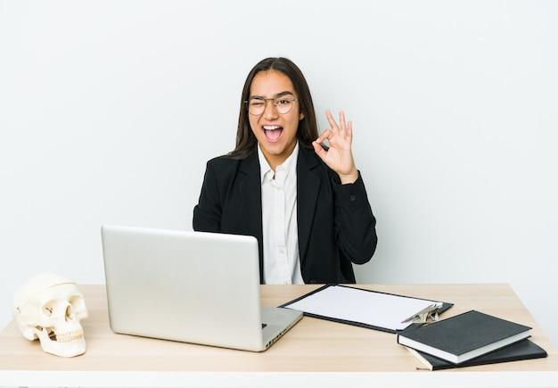 Азиатская женщина молодой травматолог, изолированные на белом фоне подмигивает и держит хорошо жест рукой.