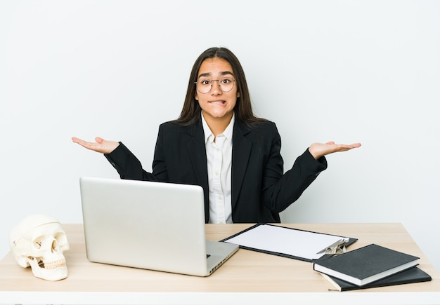 Молодая азиатская женщина травматолога изолирована на белой стене в замешательстве и сомнительно пожимает плечами, чтобы держать копию пространства