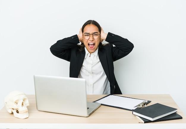 Азиатская женщина молодой травматолог изолирована на белой стене, закрывающей уши руками, пытаясь не слышать слишком громкий звук.