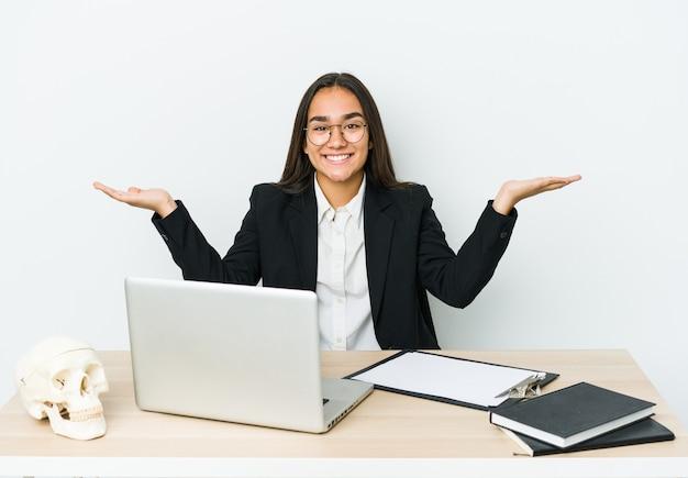 Азиатская женщина молодой травматолог изолирована на белой стене делает весы руками, чувствует себя счастливой и уверенной