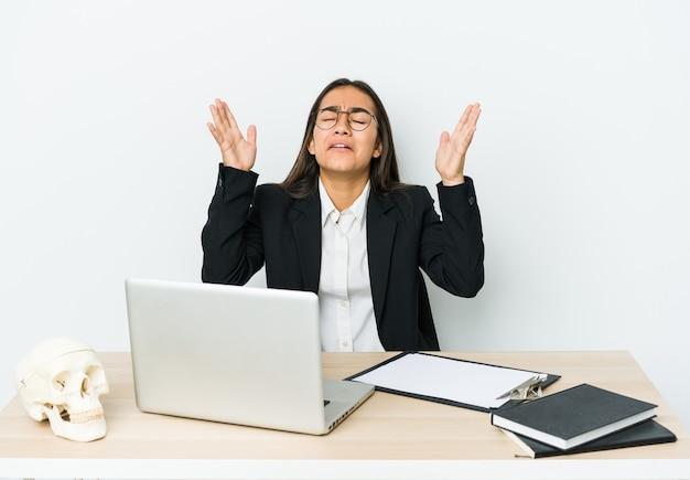 Азиатская женщина молодой травматолог изолирована на белой стене кричит в небо, глядя вверх, разочарование