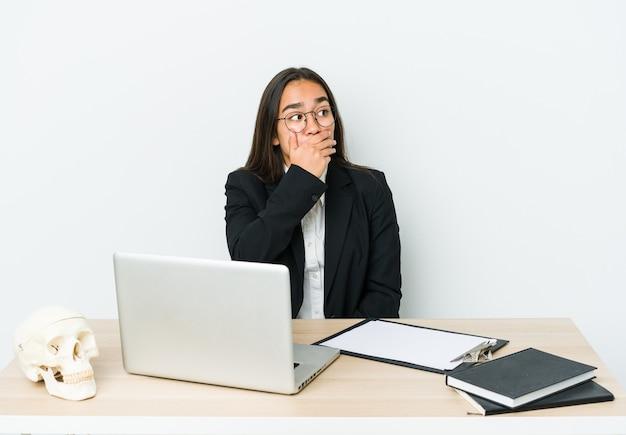 手で口を覆うコピースペースを思慮深く見ている白い壁に隔離された若い外傷学者アジアの女性。