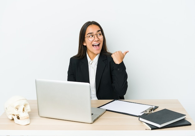 Young traumatologist asian woman isolated on white points with thumb finger away, laughing and carefree.