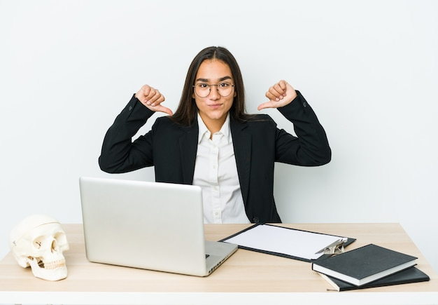 Young traumatologist asian woman isolated on white wall feels proud and self confident, example to follow.