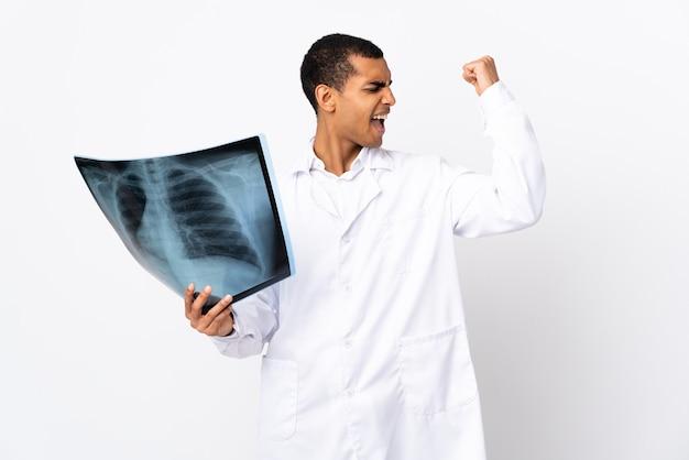 Молодой травматолог над изолированной белой стеной делает сильный жест