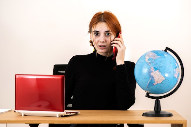 Young travel agent woman sitting behind working desk with laptop computer and geographic globe of the world talking on a cell phone.
