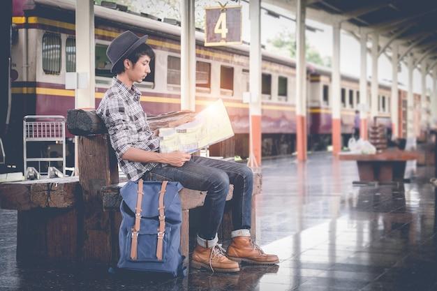 젊은 여행지도와 함께 앉아. train.vintage 필터에 여행 가방 여행.