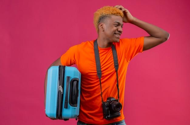 ピンクの壁の上に立っているミスのために彼の頭を引っかいて笑ってよそ見よそ見スーツケースを保持しているオレンジのtシャツを着ている若い旅行者少年