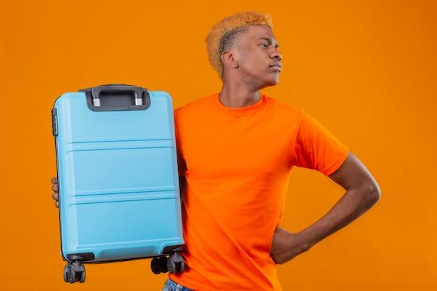 Молодой путешественник мальчик в оранжевой футболке держит чемодан, глядя в сторону с серьезным лицом, стоящим над оранжевой стеной