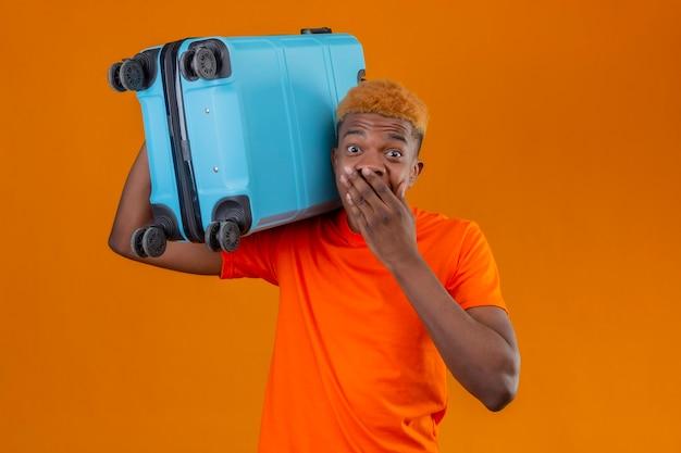 オレンジ色の壁の上に立って手で驚いて驚いて覆っている口を探しているスーツケースを持ってオレンジ色のtシャツを着ている若い旅行者少年
