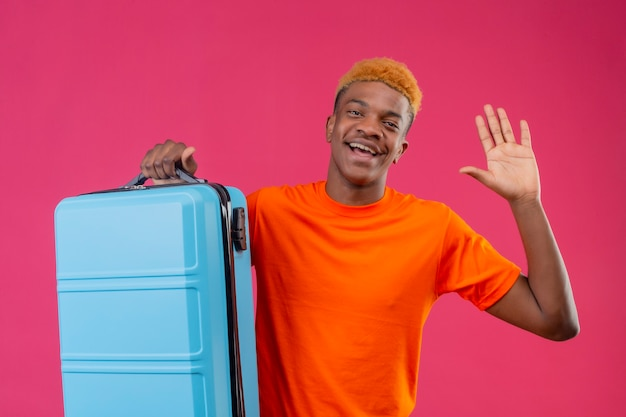 Young traveler boy wearing orange t-shirt holding suitcase smiling cheerfully waving with hand standing over pink wall