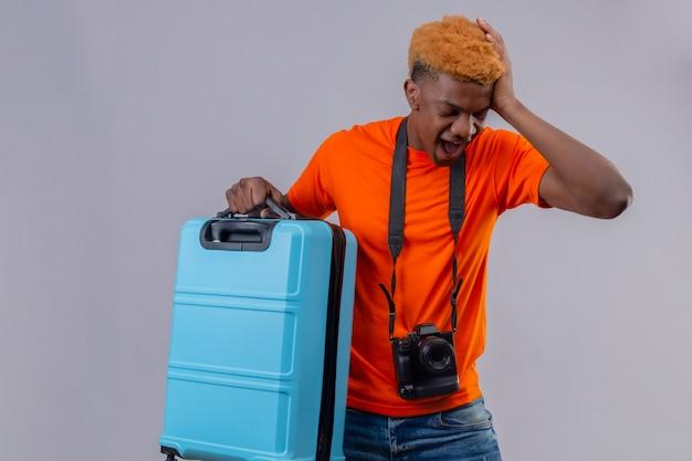 Ragazzo giovane viaggiatore che indossa la maglietta arancione che tiene la valigia in piedi con la mano sulla sua testa per errore dimenticato cosa importante