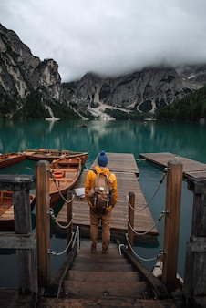 Young traveler boy with blue hat, vintage backpack and yellow raincoat on jetty of lago di braies surrounded by mountains of italian alps
