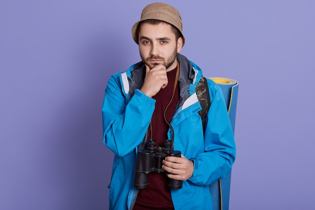 Young traveler caucasian man being confused, feels doubtful and unsure, posing against blue wall with backpack and binocular