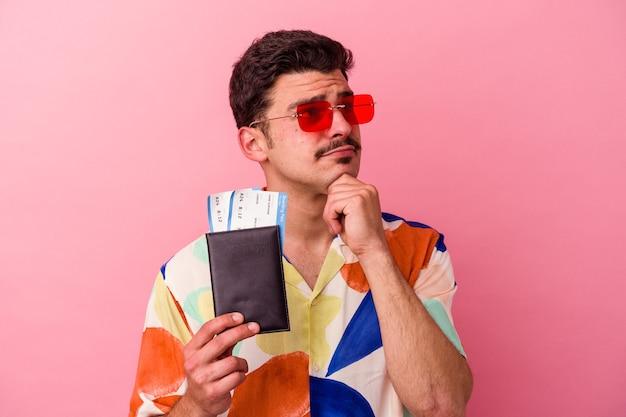Молодой путешественник кавказский мужчина держит паспорт на розовом фоне, глядя в сторону с сомнительным и скептическим выражением лица.