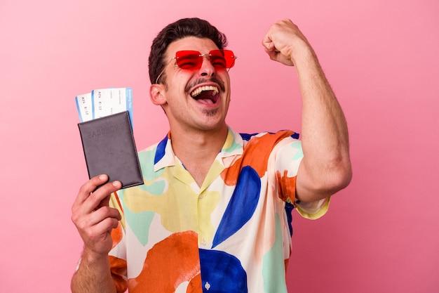 승리, 승자 개념 후 주먹을 올리는 분홍색 배경에 고립 된 여권을 들고 젊은 여행자 백인 남자.